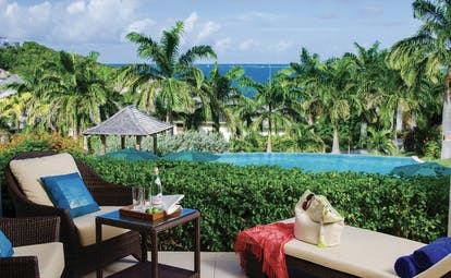 Nonsuch Bay Antigua deluxe suite balcony with lounger and chairs overlooking pool