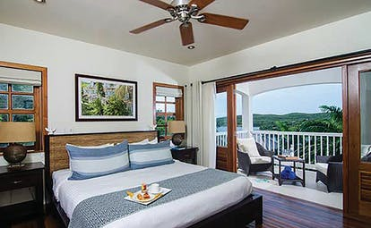 Nonsuch Bay Antigua deluxe suite bedroom leading to balcony and outdoor seating area