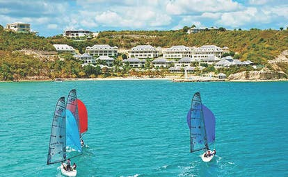 Nonsuch Bay Antigua three boats on the water hotel and beach in the background