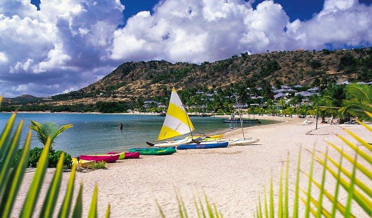 St James's Club Antigua kayaks moored on beach white sand coastline in background