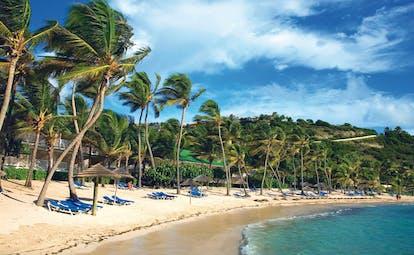 St James's Club Antigua beach white sand  sun loungers umbrellas palm trees