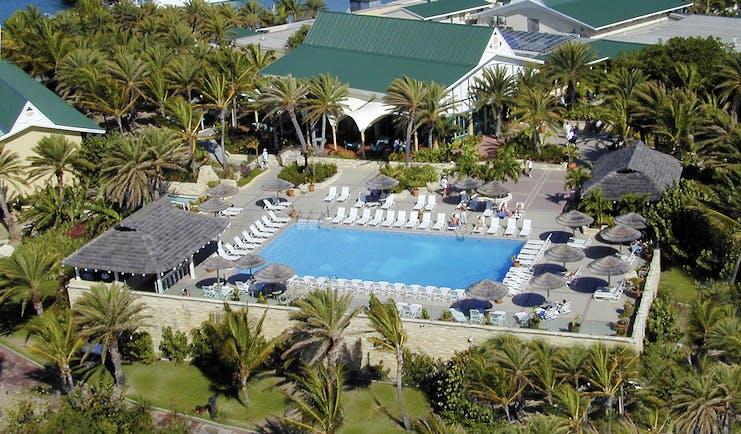 St James's Club Antigua aerial shot of pool sun loungers umbrellas palm trees