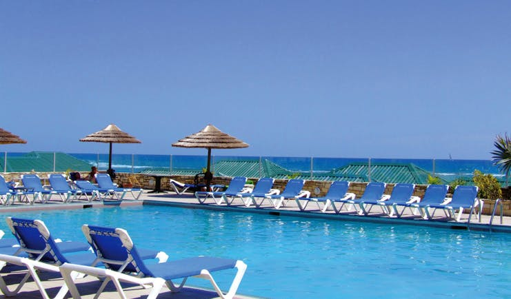 St James's Club Antigua poolside sun loungers umbrellas sea in background