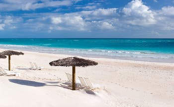 Beach in the Bahamas, white sand, clear blue sea, umbrellas