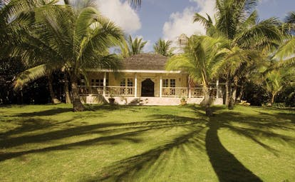 Kamalame Cay Bahamas lawn view of white bungalow and palm trees