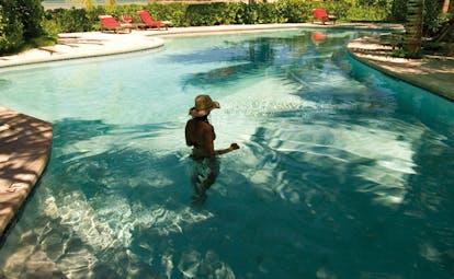 Kamalame Cay Bahamas outdoor pool loungers greenery trees