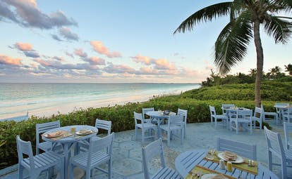 Pink Sands Bahamas blue bar outdoor dining area white tables garden and ocean view