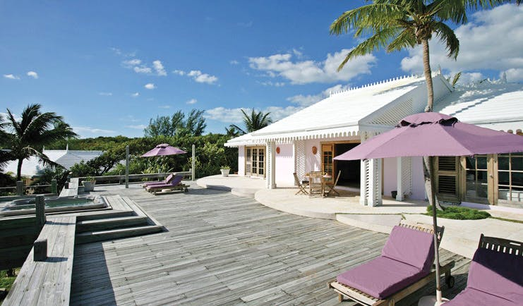 Pink Sands Bahamas deck white bungalow sun loungers umbrellas hot tub