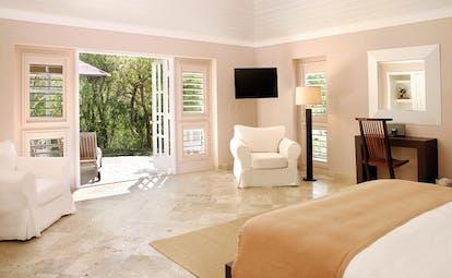 Pink Sands Bahamas garden cottage bedroom armchairs doors to patio seating area