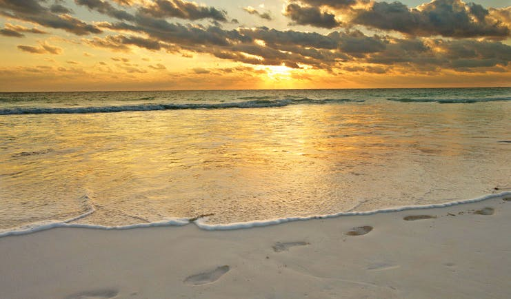 Pink Sands Bahamas sunrise over ocean footprints in the sand