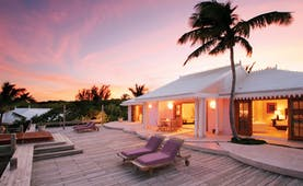 Pink Sands Bahamas villa exterior white bungalow decked area sun loungers palm trees