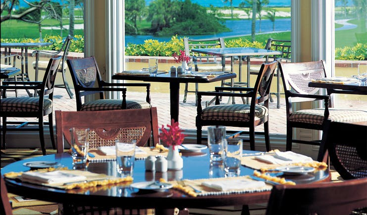 One and Only Ocean Club Bahamas clubhouse restaurant classic decor dining area with golf course view
