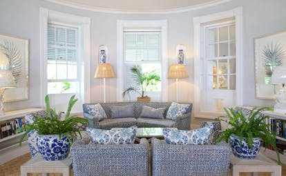 Drawing room with plants in vases, sofas and seating areas in  room with windows