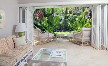 Living room area in a garden view suite with sofa in the room and doors opening onto the garden with sun loungers