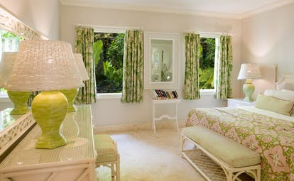 Garden view suite with double bed, lamp shades, green curtains and view of gardens out the windows