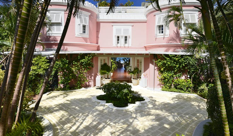 Great House with pink exterior building, white shutters covering the windows and palm trees around
