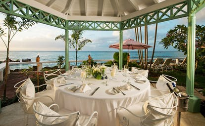 Pavilion with table set up for dining underneath and view of sea in distance
