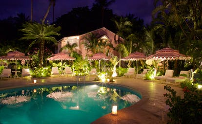 Pool at night with pink hotel exterior building in background, pink and white umbrellas and pool lights