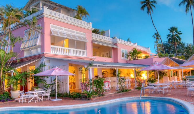 Outdoor swimming pool with pink umbrellas and deck chairs set up and pink hotel building in backgroun