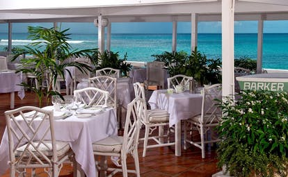 Outdoor restaurant dining area with white tables and chairs set up for dining