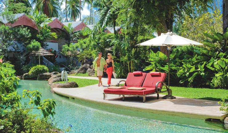 Colony Club Barbados poolside sun loungers and umbrella at side of pool