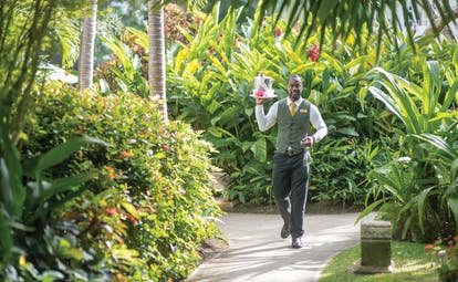 Coral Reef Club Barbados smiling waiter carrying tray and drinks across the gardens