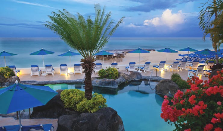Crystal Cove Barbados pool with sun loungers and umbrellas views of the beach