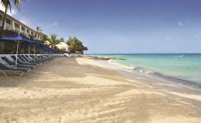 Fairmont Royal Pavilion Barbados beach with sun loungers and umbrellas