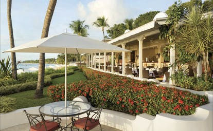 Fairmont Royal Pavilion Barbados outdoor seating beach and restaurant in background