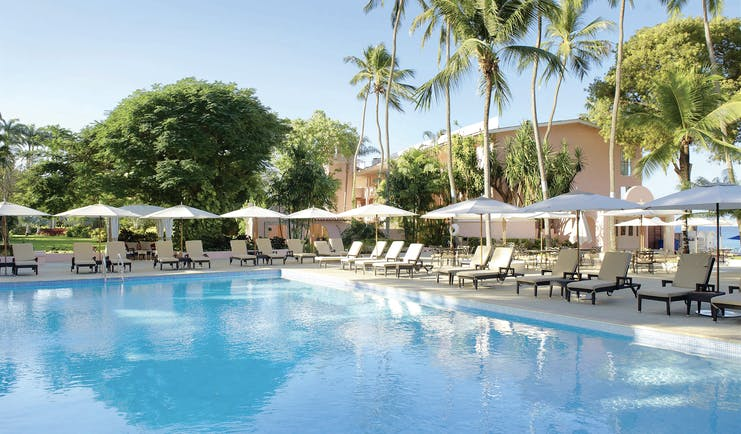 Fairmont Royal Pavilion Barbados pool sun loungers umbrellas and palm trees