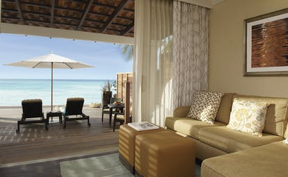 Fairmont Royal Pavilion Barbados suite lounge with private terrace and sun loungers facing the ocean