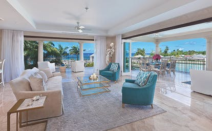Lounge area of a suite with blue and cream armchairs and sofas on top of a patternered rug looking out over the sea