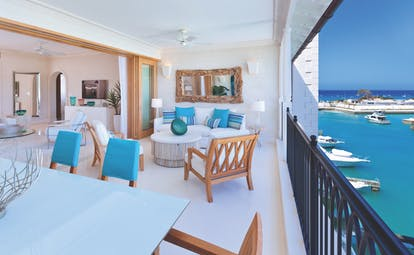 Patio in a  suite level room with tables and chairs laid out looking over clear blue water