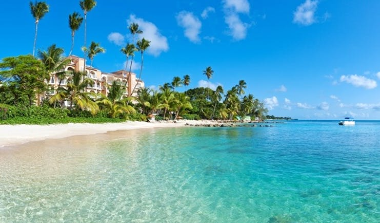 Exterior shot of St Peters Bay, hotel building in background, white sandy beach, palm trees