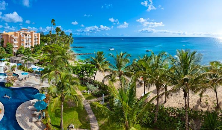 Aerial shot of St Peters Bay resort, pools, palm trees, hotel buildings, sea in background