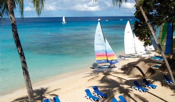 Tamarind Barbados beach white sand clear blue ocean sun loungers boats palm trees