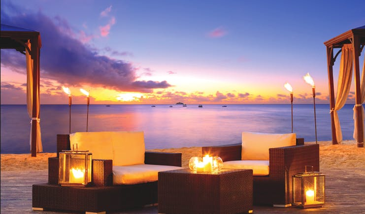The House Barbados outdoor seating area on the beach at sunset