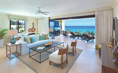 Sandpiper Barbados beach lounge indoor seating area leading to terrace with sun loungers overlooking the ocean
