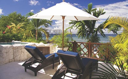 Sandpiper Barbados lounge chairs and umbrella overlooking the ocean