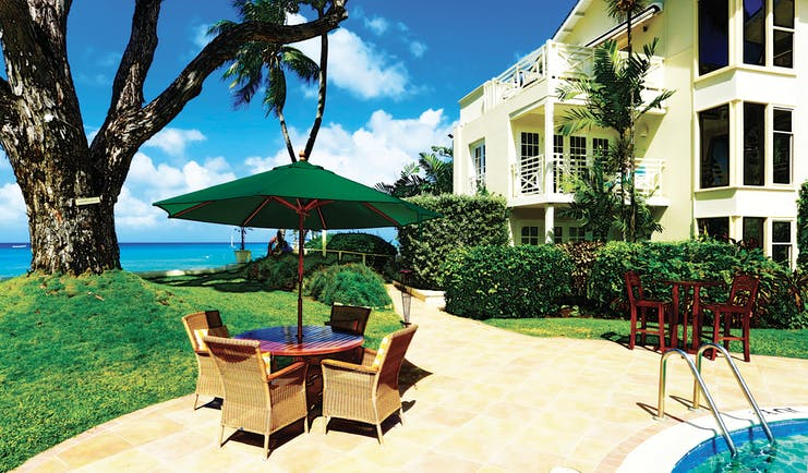 Treasure Beach Barbados outdoor dining area beside pool with views of the ocean