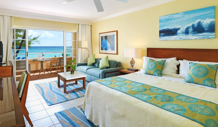 Turtle Beach Barbados ocean view junior suite bedroom with lounge area opening up to balcony overlooking the ocean