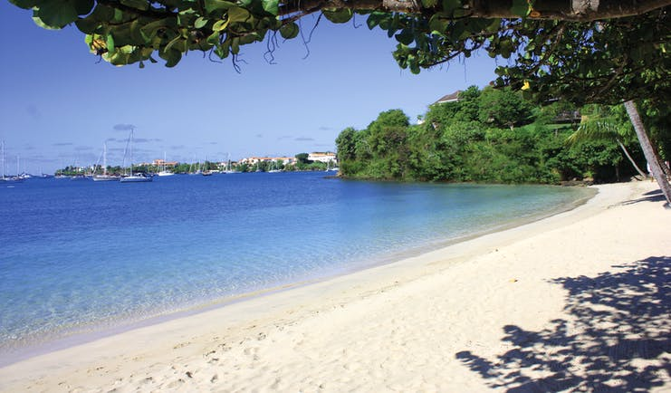 Calabash Grenada beach sandy beach and clear blue ocean boats on the water in the background