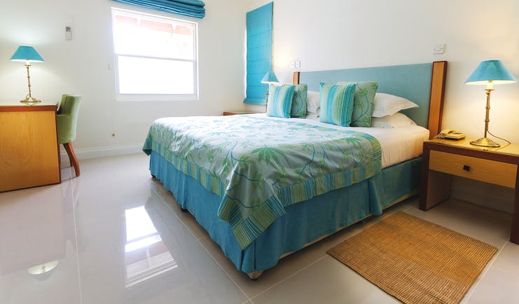 Calabash Grenada suite bedroom double bed and lounge area leading to balcony