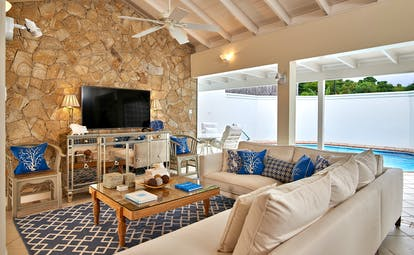 Living room with stone wall and ceiling fan