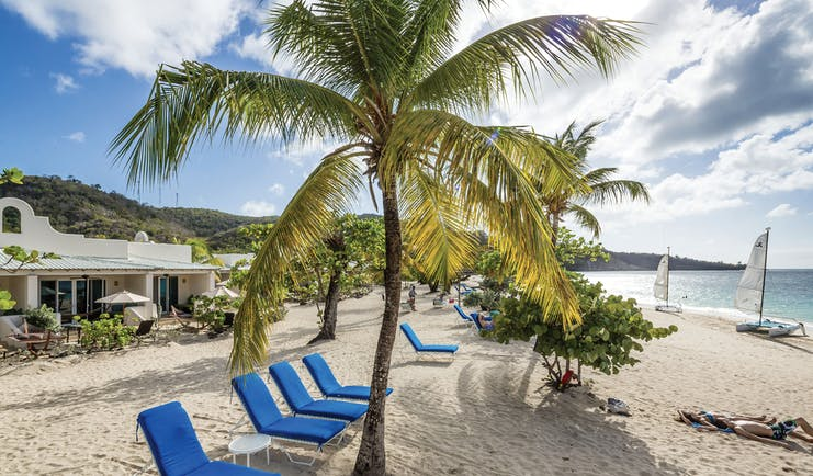 Spice Island Grenada loungers on the beach in the shade of palm trees