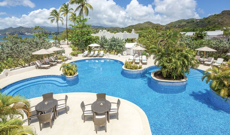 Spice Island Grenada pool with sun loungers and outdoor seating areas