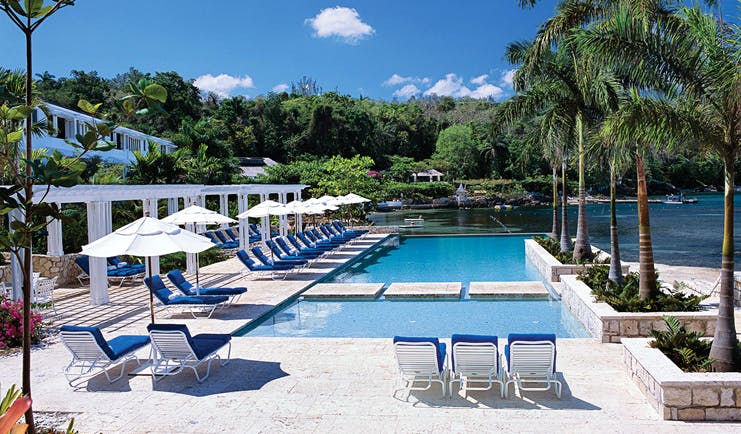 Round Hill Jamaica pool sun loungers and umbrellas views of the ocean