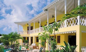 Four Seasons Nevis exterior yellow building greenery pool