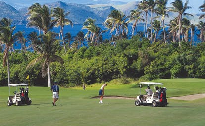 Four Seasons Nevis golf course golfers golf buggies palm trees and mountains in the background