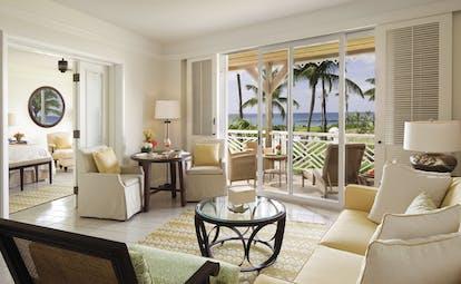 Four Seasons Nevis Indigo suite lounge area opening onto balcony overlooking gardens